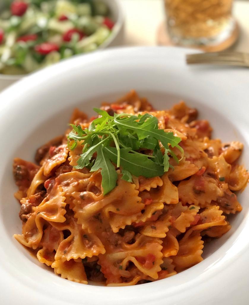 Pasta farfalle met gehakt in een romige tomatensaus